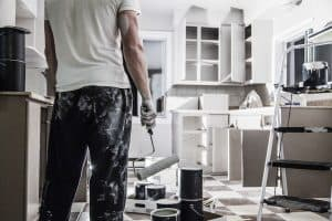 man holding paint roller, looking at kitchen cupboard repainting project - stock image