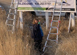 Erin at job site helping with attaching a new sign